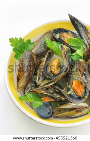 Mussel soup with fresh parsley on white background