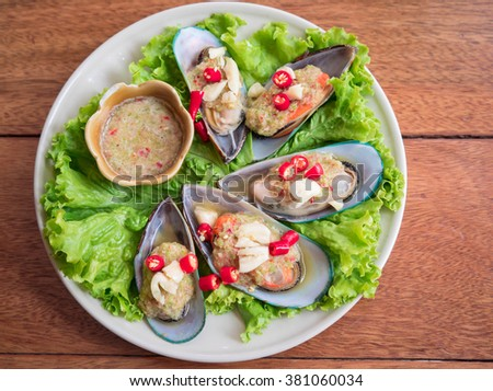 Mussels and Spicy Dipping Sauce On Wood Background - stock photo