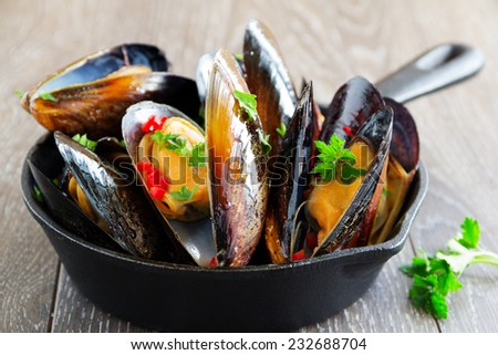 Mussels cooked in wine with parsley. - stock photo