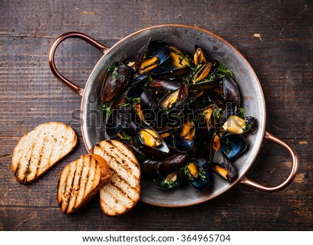 Mussels in copper cooking dish and bread toasts on dark wooden background - stock photo