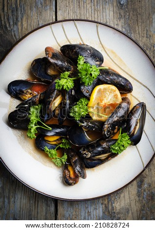Mussels in tomato sauce on rustic wooden table - stock photo
