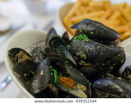 Mussels in White Wine and Garlic with Out of focus French fry and beer on the table. Mussels, cooked in white wine with aromatic herbs from Provence, French fries and a glass of beer - stock photo