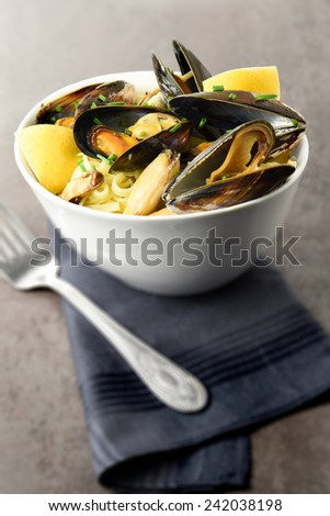 Mussels linguine with chives in a rustic setting with antique fork and napkin. - stock photo