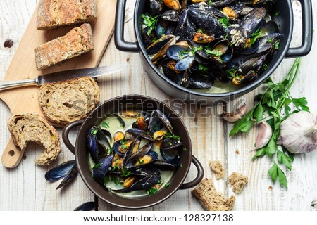 Mussels meal served with bread by the sea - stock photo