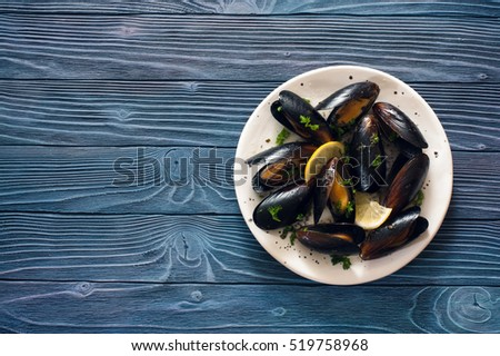 Mussels on white plate over blue wood background. Top view