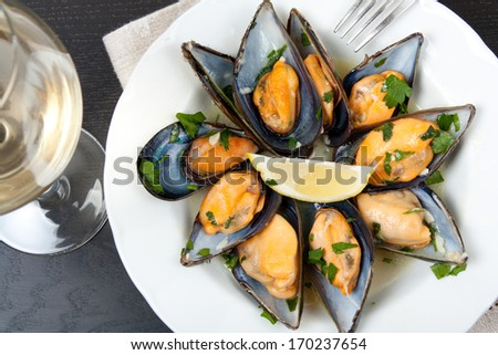 Mussels with white wine and parsley sauce with a glass of white wine