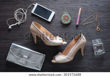 Must have for party night. Overhead of essentials for modern young woman. Different objects on wooden background: silver clutch, smartphone, heels and parfume. - stock photo