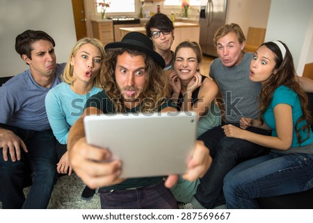 Mustache man with group of friends taking a selfie on a tablet and make funny faces