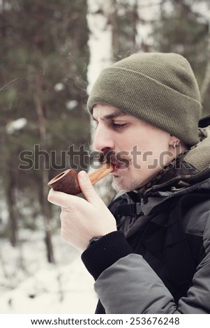 Mustached man smoking a pipe in winter forest - stock photo
