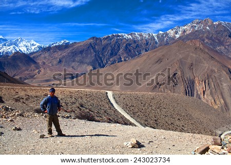 MUSTANG, ANNAPURNA CONSERVATION AREA, NEPAL - DECEMBER 26: Trekker on the road from Muktinath to Jomsom, a part of Annapurna Circuit trek on December 26, 2009 in Annapurna conservation area, Nepal.  - stock photo