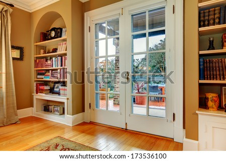 Mustard and white entrance hall with arch built-in wall shelves, hardwood floor and wide wooden glass door
