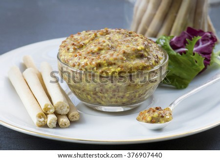 Mustard in a glass dish with a silver spoon on a white bone china plate, with bread sticks and salad. Shot with a selective focus in window light .Room for text top left  - stock photo