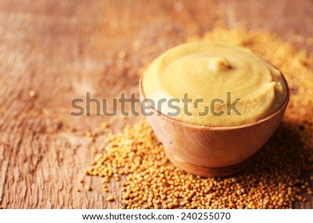 Mustard in bowl on wooden background - stock photo