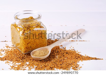 Mustard in glass jar and mustard powder in spoon on wooden background - stock photo