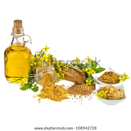 Mustard oil jar and powder spoon, seeds scoop with fresh mustard flower on white - stock photo