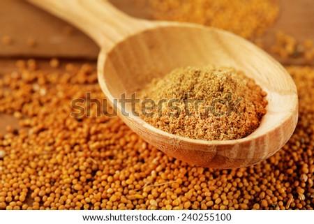 Mustard powder in wooden spoon on mustard seeds, on  wooden background - stock photo