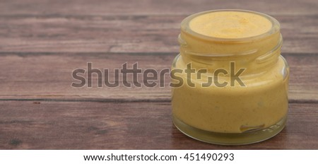 Mustard sauce in mason jar over wooden background