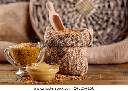 Mustard seeds in bag and sauce in sauce-boat on  wooden background - stock photo