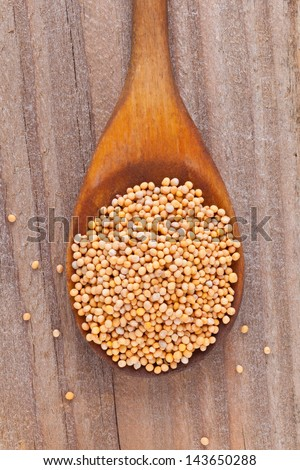 Mustard seeds on wooden spoon on rustic kitchen table - stock photo
