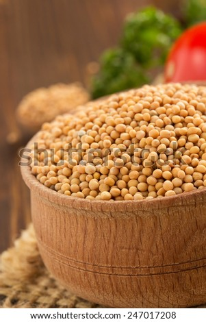 mustard spices on wooden background - stock photo