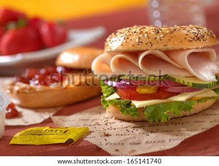 Mustard with a turkey bagel - stock photo