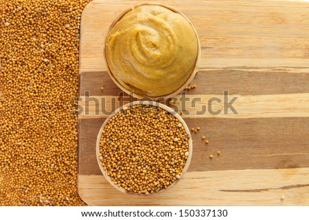 Mustard with seeds on wooden background - stock photo