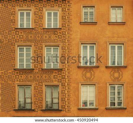 Mustard yellow aged old building facade with multiple windows. Historical city elements. Classic european architecture. Postcard concept. Travel inspiration. Estate rent sale concept background.