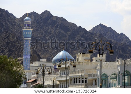 Mutrah minaret against a mountain backdrop, in Mutrah, Muscat, Oman, Middle East - stock photo