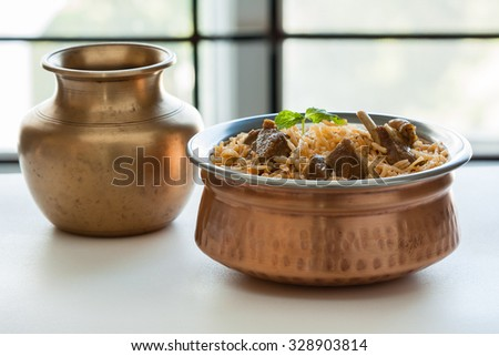 Mutton biryani - Closeup view of delicious mutton (lamb) biryani with mint garnish and served in authentic copper bowl. Natural light used. - stock photo
