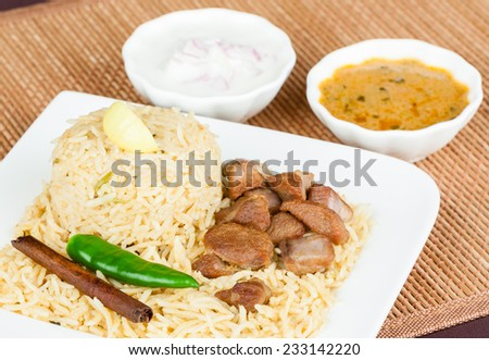 Mutton Biryani with Salad - Closeup view from the top of delicious mutton (lamb) biryani with garnish and served with salad (raita) and gravy. Innovative presentation. Shallow DOF. - stock photo