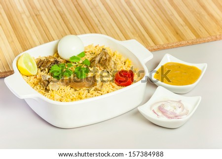 Mutton Biryani with Salad & Egg - Full view of delicious mutton (lamb) biryani garnished with tomato peel, cilantro and lemon. It is served with hard boiled egg, onion salad (raita) & vegetable curry. - stock photo