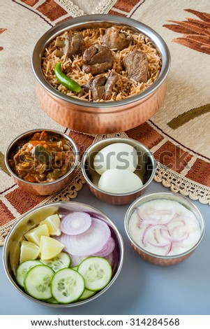 Mutton biryani with traditional sides - Overhead view from the top of delicious mutton (lamb) biryani served in authentic copper utensils with salad (raita), gravy and egg. Natural light used. - stock photo