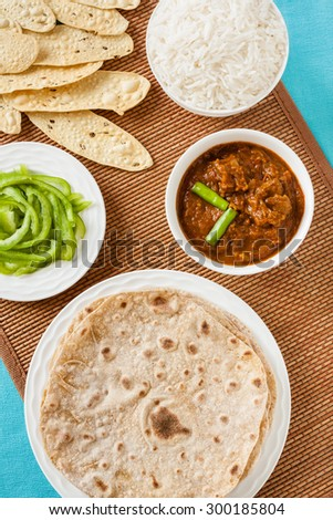 Mutton rogan josh meal - Overhead view of Indian mutton rogan josh meal with rice and chapati. This spicy hot Kashmiri dish uses red chilli (cayenne pepper) as its main ingredient. Natural light used. - stock photo