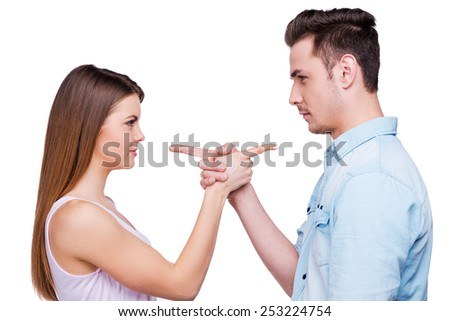 Mutual claims. Side view of beautiful young loving couple pointing each other while standing against white background  - stock photo