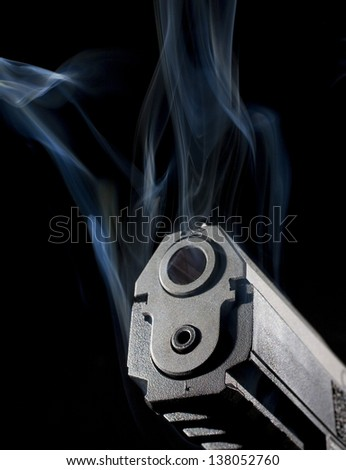 Muzzle of a pistol that is surrounded by blue smoke - stock photo