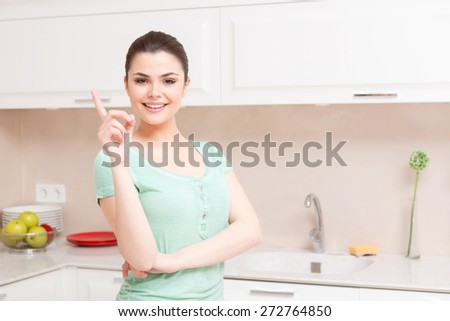 My advice to you. Beautiful woman standing in white colored kitchen with one hand raised