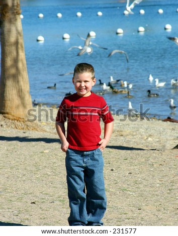 MY BOY MATTHEW STANDING ON THE SAND IN LAKE HAVASUE. - stock photo