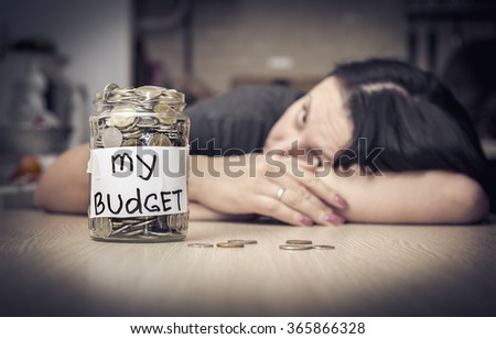 My budget. Coins in glass money jar,  teenager girl in the background - stock photo
