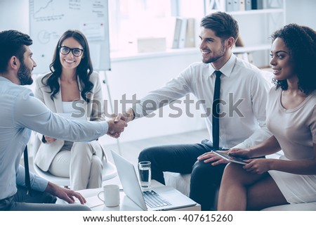 My congratulations! Two handsome men shaking hands with smile while sitting on the couch at office with their beautiful coworkers - stock photo