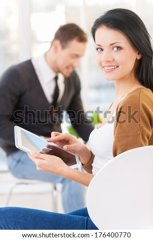 My digital assistant. Confident young businesswoman in casual wear using digital tablet and smiling while his colleagues working on the background