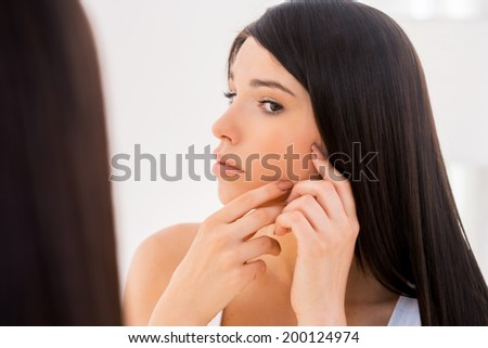 My face should be perfect. Attractive young woman examining her face while looking at the mirror - stock photo