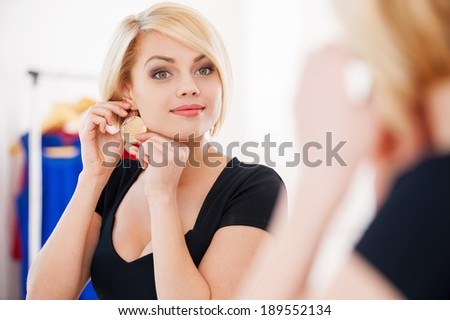 My favorite earrings! Beautiful young blond hair woman wearing earrings and smiling while looking at the mirror - stock photo