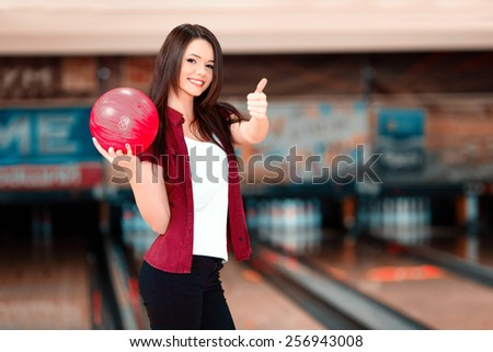 My favorite game. Beautiful young women holding a bowling ball while standing against bowling alleys and showing her thumb up - stock photo