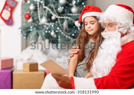My favorite granddaughter. Pleasant cheerful girl sitting with Santa and reading the card with Christmas tree standing in the background - stock photo