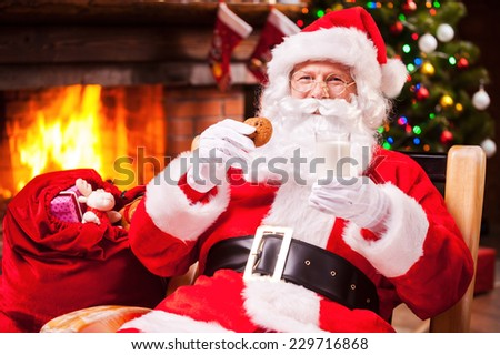 My favorite meal! Cheerful Santa Claus holding glass with milk and cookie while sitting at his chair with fireplace and Christmas Tree in the background  - stock photo