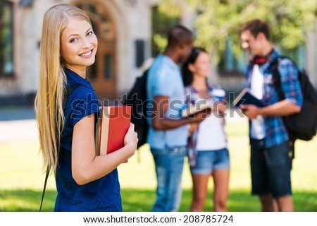 My future is in my hands. Beautiful young woman holding books and smiling while standing near university building and with her friends chatting in the background  - stock photo