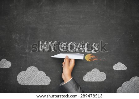 My goals concept on black blackboard with businessman hand holding paper plane