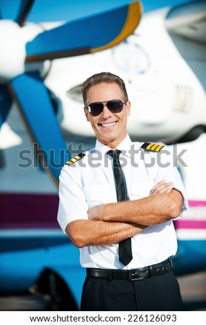 My job is my passion. Confident male pilot in uniform keeping arms crossed and smiling while standing in front of the airplane