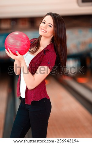 My lucky ball. Beautiful young women holding a bowling ball while standing against bowling alleys