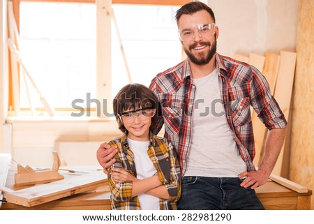 My professional follower. Cheerful young male carpenter embracing his son while standing in workshop - stock photo